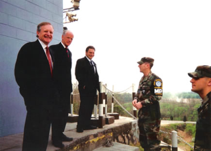 Lamont Colucci, PhD, former Dept of State diplomat, stands at the demilitarized zone of North and South Korea with then-Governor of Oklahoma.
